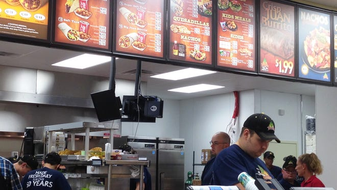Employees at TacoTime prepare food during a soft opening Sunday.