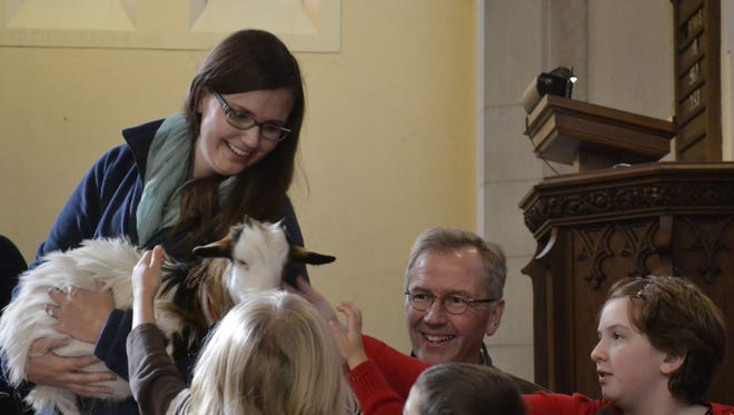 Children pet Mamie, one of two small goats brought to the worship service Sunday at Union Congregational United Church of Christ in Green Bay. Mamie and Ava, who came from a farm in Ledgeview and were handled by Matt Lyman, second from right, and his daughter Laura, top left, were displayed as part of the church's annual Heifer Living Gift Market after the service in support of Heifer International.