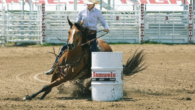 Beau Peterson rides her horse, Barbie, around the barrel in the barrel race competition during slack events Tuesday morning at the Pretty Prairie Rodeo. Peterson's time was 17.72.