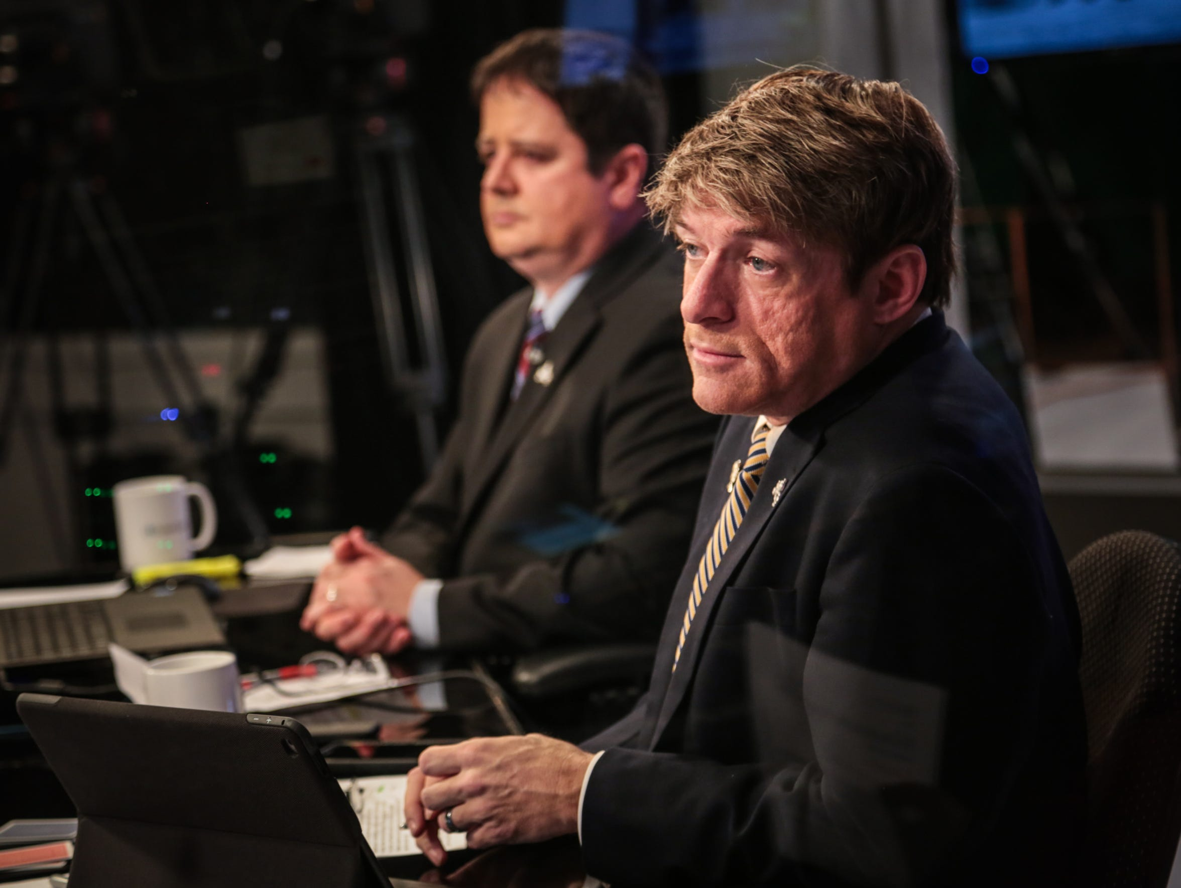 Panelists Bradley Eli, left, and Michael Voris watch