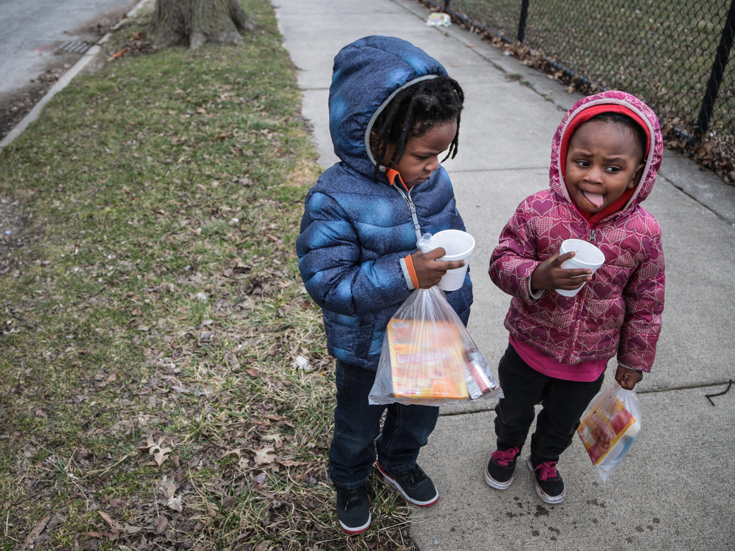 Miyake Young, 3, of Detroit, and his sister Malaysia Foley, 2, of Detroit, get their hot chocolate and bagged lunch from the Salvation Army's Bed and Bread program food truck on Detroit's east side. The truck brings meals every day of the year to several dozen stops in Detroit's poorest neighborhoods.
