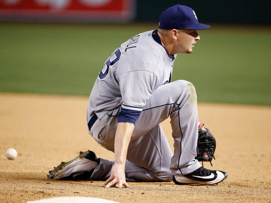 San Diego Padres' Trevor Cahill kneels on the ground after losing control of a ball thrown to him at first base on a hit by Arizona Diamondbacks' Brandon Drury during the fifth inning of a baseball game, Wednesday, April 26, 2017, in Phoenix. (AP Photo/Ross D. Franklin)