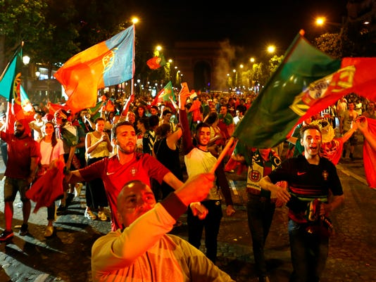 Supporters of Portugal celebrate their team's 1-0 win over France on the Champs Elysees avenue in Paris after the Euro 2016 final soccer match between Portugal and France, Monday, July 11, 2016. Portugal wins the 2016 European Championship, after substitute Eder scored in extra time to give his team a 1-0 win over France. (AP Photo/Francois Mori)