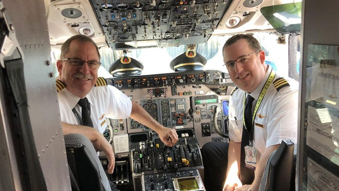 Jim Hamilton, left, is seen with his son Chris, also a pilot for Delta Airlines. The elder Hamilton flew into history this week when he piloted the last commercial flight of a McDonnell Douglas MD 88 in the United States.