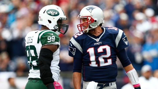 New England Patriots quarterback Tom Brady (12) speaks to New York Jets outside linebacker Quinton Coples (98) during the first half at Gillette Stadium.