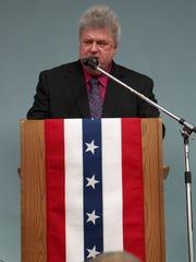 Robert Nueske speaks at the rededication ceremony for