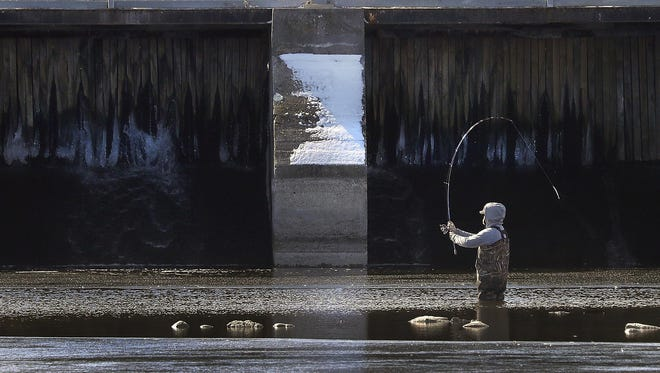 A man braves the cold water March 8 while fishing near the WG Bryan Bridge in Neenah.