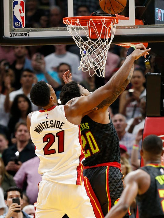 Miami Heat center Hassan Whiteside (21) tips in a ball from behind Atlanta Hawks forward John Collins (20) during the second half of an NBA basketball game Tuesday, April 3, 2018, in Miami. Whiteside's tip-in with a minute left put Miami up for good and the Heat clinched their 20th playoff spot in 30 seasons by rallying to win 101-98. (AP Photo/Wilfredo Lee)