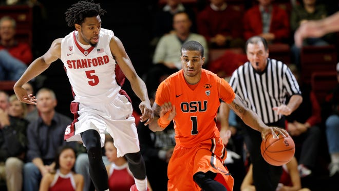 Oregon State guard Gary Payton II (1) dribbles next to Stanford guard Chasson Randle (5) during the first half of an NCAA college basketball game Thursday, Feb. 26, 2015, in Stanford, Calif.