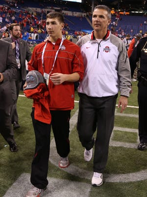 Ohio State Buckeyes coach Urban Meyer walks off the field with his son Nate Meyer after the game against the Wisconsin Badgers during the Big Ten Football Championship game at Lucas Oil Stadium in December of 2014.
