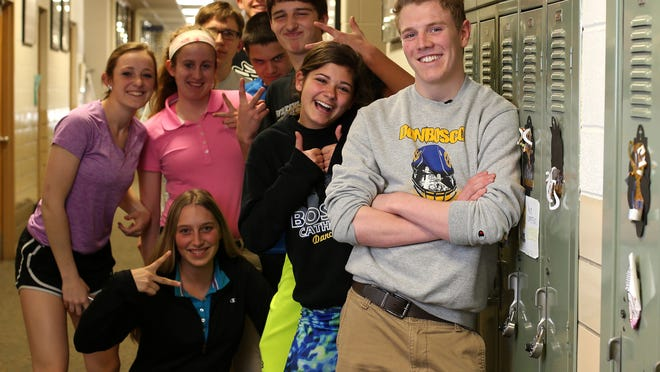 Cole Fox, a senior at Don Bosco High School in Gilbertville, poses for a photo as friends and classmates photobomb him on Friday, April 10, 2015. Fox is a two-time state qualifying wrestler for the Dons, and recently came out as a homosexual. He said the support from his friends and family has meant a lot to him.