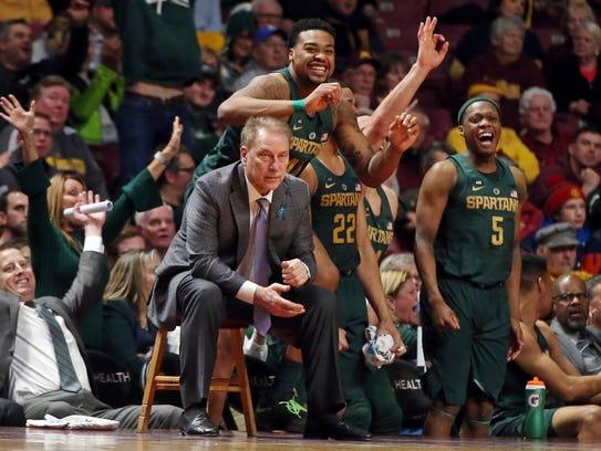 Michigan State players celebrate behind coach Tom Izzo