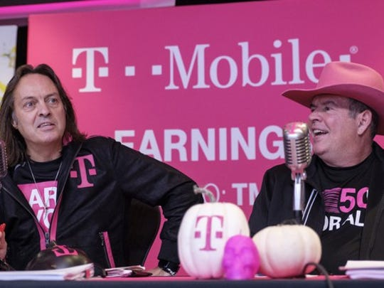 T-Mobile CEO John Legere and CFO Braxton Carter sitting in front of microphones.