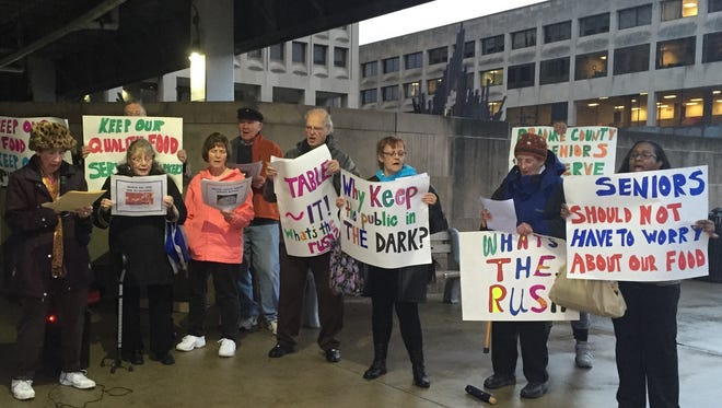 Demonstrators outside the Broome County Office Building call on legislators to delay a vote on an outsourcing resolution Thursday.