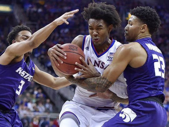 Devonte' Graham forces his way between Kansas State defenders on his way to the basket March 9 during the Big 12 tournament in Kansas City, Mo.