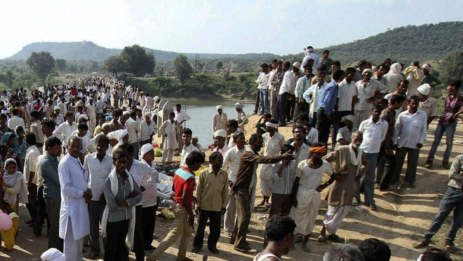 Indian villagers gather after a deadly stampede on a bridge across the Sindh River on Sunday.