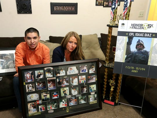 Aaron Diaz, left, and his mother, Amber Diaz, hold photographs of U.S. Army Cpl. Isaac Diaz, who was killed in active duty on Dec. 1, 2004. Aaron Diaz was just 3 when his father died in Afghanistan.