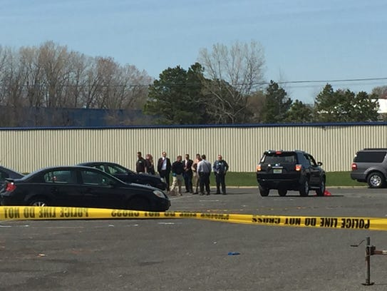 Investigators huddle late Tuesday afternoon behind