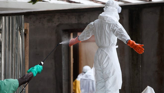 A Liberian nurse in protective clothing is sprayed with disinfectant after preparing several bodies of victims of Ebola for burial in the isolation unit of the ELWA Hospital in Monrovia, Liberia.