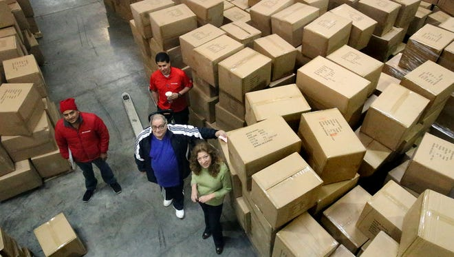 In this file photo, Liz Veliz, lower right, administrator for Operation Noel, stands among the many boxes of coats that were donated and delivered to area children.