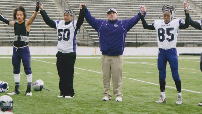 Pontiac High School varsity football coach John Lloyd, center, died suddenly in his Rochester Hills home on Nov. 5 of a brain aneurysm.