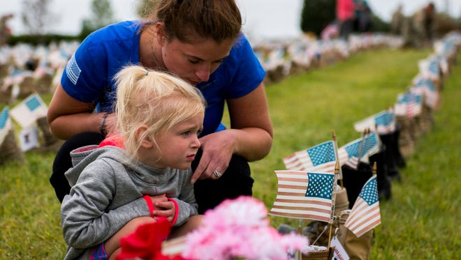 Samantha Houck, wife of Sgt. Eric M. Houck, and their daughter Violet kneel by his boot during a ceremony for fallen soldiers at Fort Campbell on September 11, 2017. Houck was one of three Rakkasan soldiers killed June 10 in northeastern Afghanistan by a rogue Afghan Police officer.