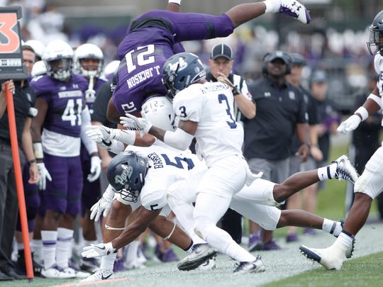 Wolf Pack defensive back Dameon Baber (5) tackles Northwestern running back Justin Jackson (21) during the second quarter at Ryan Field on Saturday.