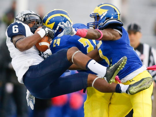 Delaware defensive backs Ryan Torzsa (center) and Tenny Adewusi dump New Hampshire receiver Kyon Taylor out of bounds to force a punt in the third quarter of the Blue Hens' 31-14 win at Delaware Stadium in 2015.