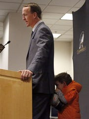 Should I have done this? Marshall Manning gets shy and hides behind his father during a press conference.