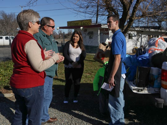 """Bill and Vicki Wilkinson, left, of Palo Cedro drop off donations for Jose """"Tony"""" De La Torre, right, while Araceli Oscguera, center, looks on. De La Torre and his three young children lost everything they own when their house burned down in the Anderson area Wednesday."""