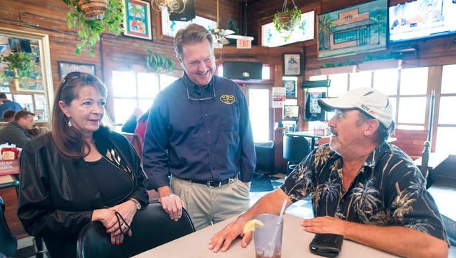 Owners Donna and Hub Stacey chat with regular customer Bill Baker at their Hub Stacey's Food & Spirits restaurant in downtown Pensacola on Thursday, March 8, 2018.  They will be celebrating the restaurant's 20th anniversary on March 24th.