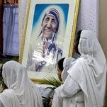 Nuns of Missionaries of Charity, the order founded by Mother Teresa, portrait seen, join in a special mass in relation to her canonization, beside her tomb in Kolkata, India, Tuesday, March 15, 2016 Mother Teresa will be made a saint on Sept. 4. Pope Francis set the canonization date Tuesday, paving the way for the nun who cared for the poorest of the poor to become the centerpiece of his yearlong focus on the Catholic Church's merciful side. (AP Photo/ Bikas Das)