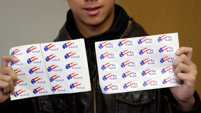A student clerk offers stickers to voters at a fire station in Stockton, Calif., a state that has one of the biggest populations of Hispanic voters in the country.