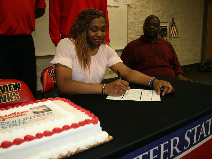 Rossview star Jemiah Harrison sits at the signing table with a cake during her ceremony at Rossview High School Wednesday.