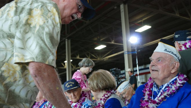 Pearl Harbor survivor Robert Irwin shakes the hand of his brother, Frank Broz, on Monday, Dec. 7, 2015, in Pearl Harbor, Hi., before a ceremony marking the 74th anniversary of the Japanese attack that launched the U.S. into World War II.