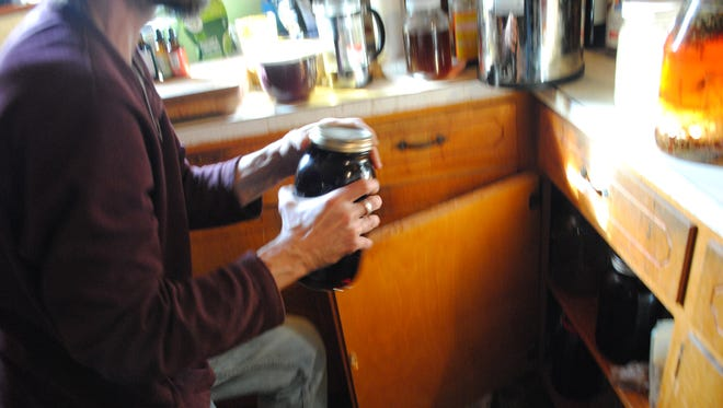 Bo Fain, co-owner of Smarty Plants, checks on a batch of elderberry tincture Thursday. He and wife Ruthie have been extra busy since flu season began making elderberry and immune boosting products.