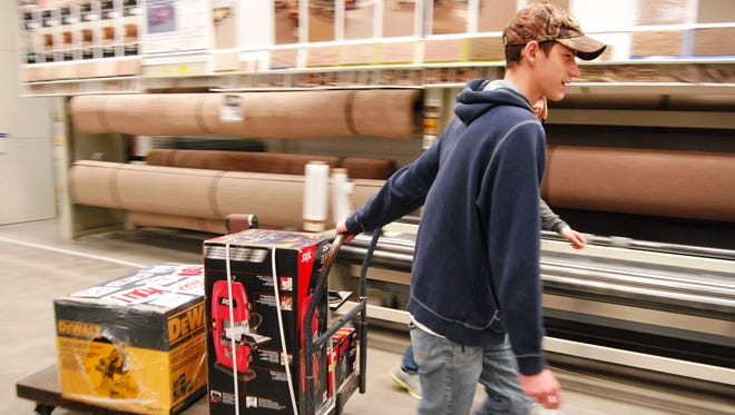Marysville High School seniors Keaton Weingartz and Greg Francois haul a cartload of equipment at the Lowe's store in Fort Gratiot.