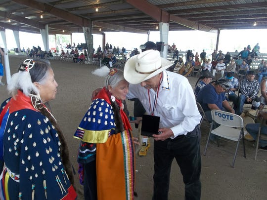 Fort Peck Tribal Chairman Rusty Stafne presents a silver medal from the U.S. Mint to the family of the late Gerald Red Elk, who served as a code talker in the Montana National Guard's Company B,. 163rd Infantry Regiment. Renee Yellow Man, left, and Margaret Red Elk accepted the medal at the ceremony honoring 48 Fort Peck code talkers Saturday in Poplar. For the