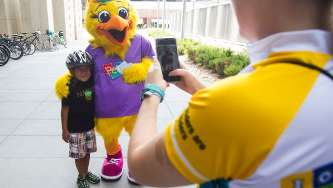 Perky poses for photos with children during a bike safety event hosted by members of the UI Stead Family ChildrenÕs HospitalÕs RAGBRAI team team on Tuesday, July 17, 2018, outside the Stead Family Children's Hospital in Iowa City, Iowa.