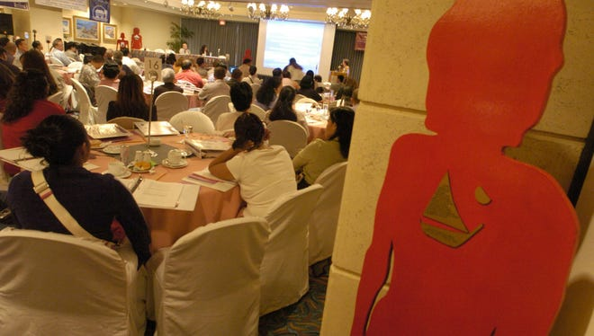 The red silhouette of a family violence victim stands behind the audience during a 2005 Family Violence Conference. Victims of family violence are often known as silent victims.