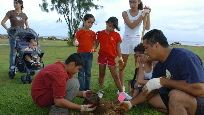 "In this August 2004 file photo, Deena Quitigua, 17; Ian Manibusan, 9 months; Nico Manibusan, 12; Kara Quitigua, 7; J'Nisha Manibusan, 8; Tanya Quitigua, 14; Lauriel Manibusan; and Roland Quitigua plant a da'ok tree at the Paseo grounds in Hagåtña. Roland Quitigua and Lauriel Manibusan, co-workers at the University of Guam, gathered their children to help pick up trash and plant trees as part of ""Island Pride,"" a monthly, multiagency effort to beautify Guam and raise awareness about the island's environment."