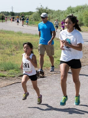 A young runner runs with a volunteer high school buddy in the summer youth running program 1-mile summer challenge series at La Llorona Park in July 2015.