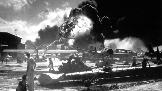 In this Dec. 7, 1941 photo provided by the U.S. Navy, sailors stand among wrecked airplanes at Ford Island Naval Air Station as they watch the explosion of the USS Shaw in the background, during the Japanese surprise attack on Pearl Harbor.