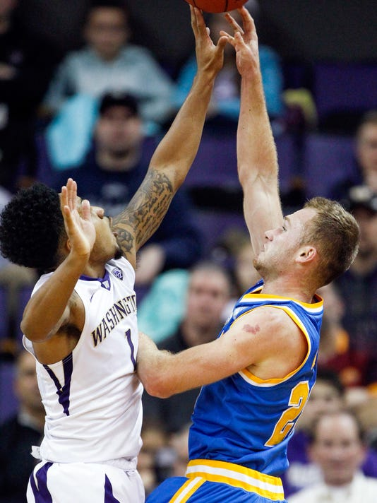 UCLA guard Bryce Alford (20) puts up a shot against Washington guard David Crisp (1) during the first half of an NCAA college basketball game Friday, Jan. 1, 2016, in Seattle. (AP Photo/Joe Nicholson)