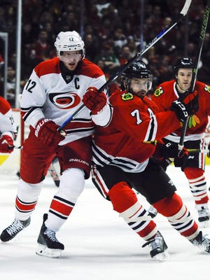 Carolina Hurricanes center Eric Staal (12) and Chicago Blackhawks defenseman Brent Seabrook (7) watch the puck in the second period at the United Center.