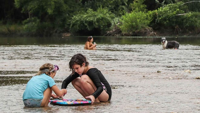 Pepper Carlton, 7, left, and Bowie Alarcon, 9, play together at Secret Beach in Austin on Monday, when temperatures in the city climbed into the high 80s but felt more like the high 90s because of increased humidity.