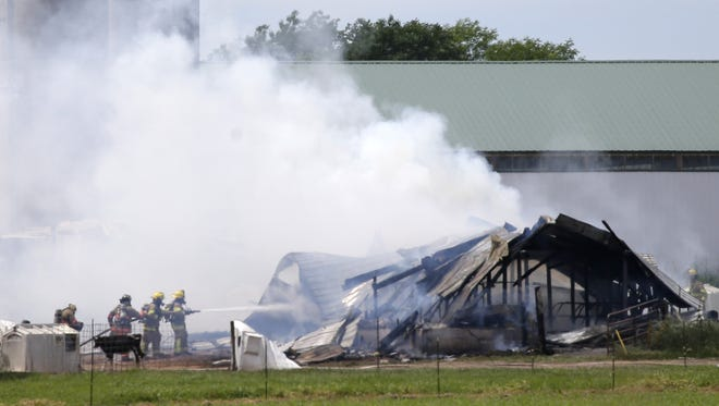 Firefighters battle a barn fire Thursday afternoon at W7410 Rock Road in the Town of Ellington.
