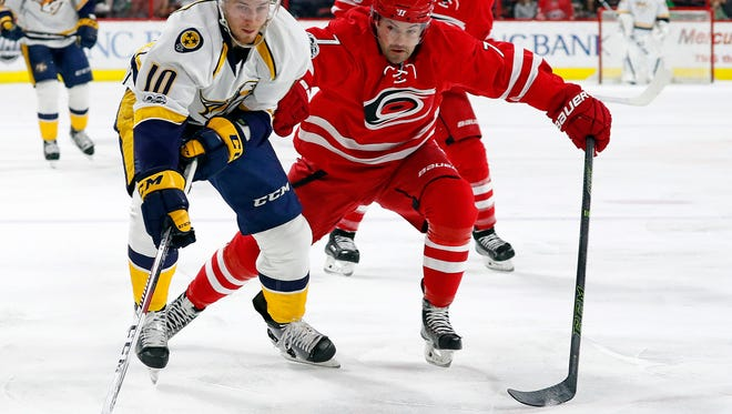 Predators forward Colton Sissons reaches for the puck as Hurricanes defenseman Ryan Murphy defends during the first period Saturday.