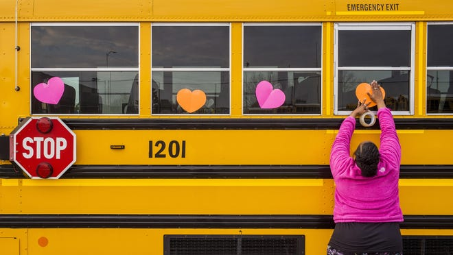 Peoria Public Schools bus driver trainer Robin Bryant attaches a heart to the window of a school bus Friday, April 3, 2020 at the school's transportation center.