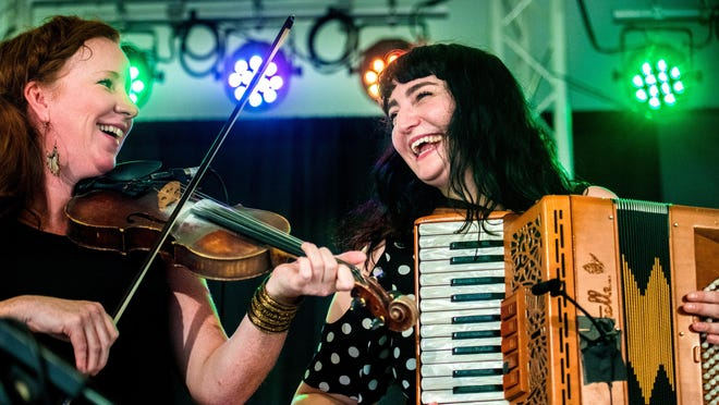 Mairi Rankin and Fiona Black laugh as the Celtic band Outside Track plays during Peoria Irish Fest on the Peoria Riverfront.